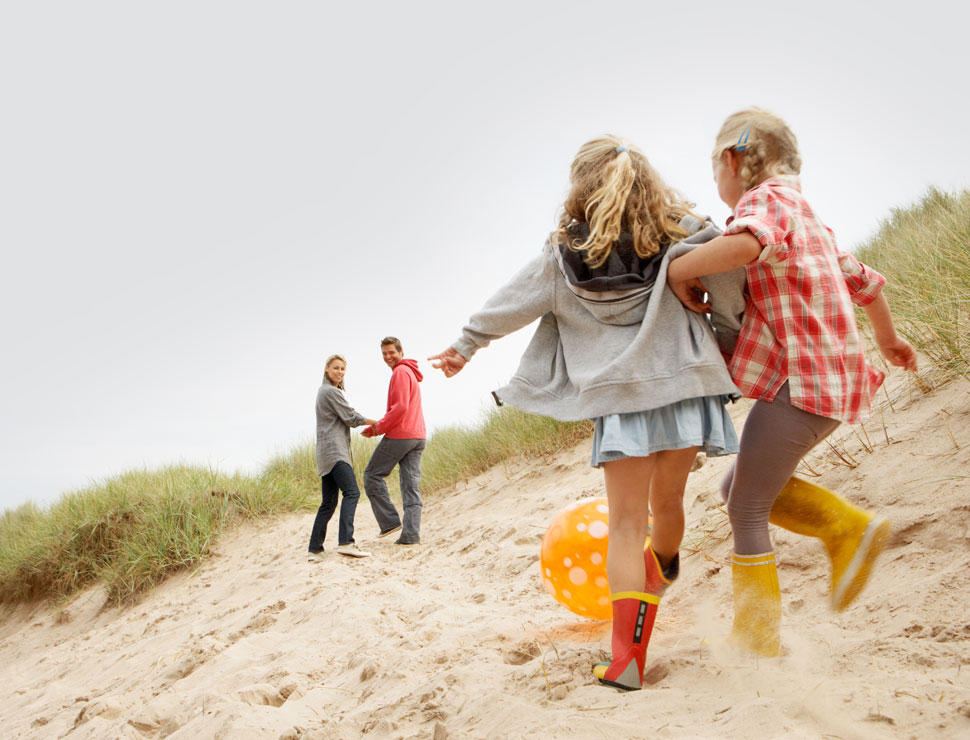 Sand dune with two fair-haired young girls and yellow beach ball in the foreground facing away looking at two adults.