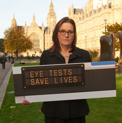 A woman holding 'Eye tests save lives' sign.