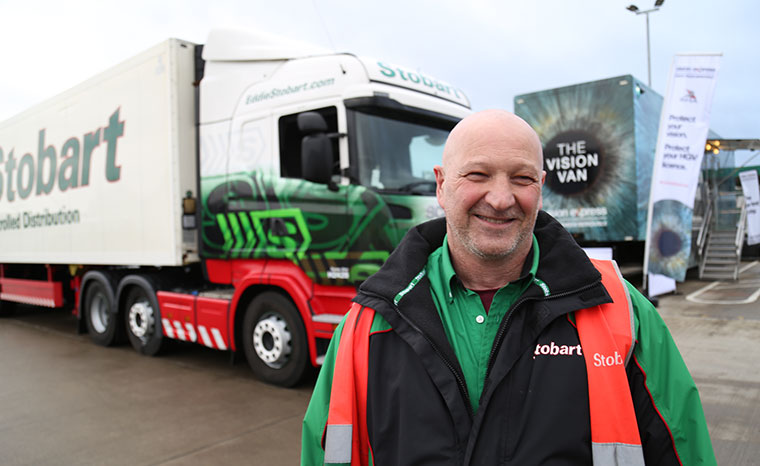 A smiling man standing in front of a truck.