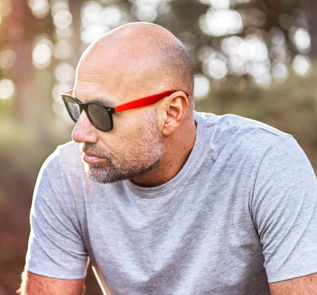 Man with beard outdoors in grey teeshirt wearing sunglasses which have red arms.