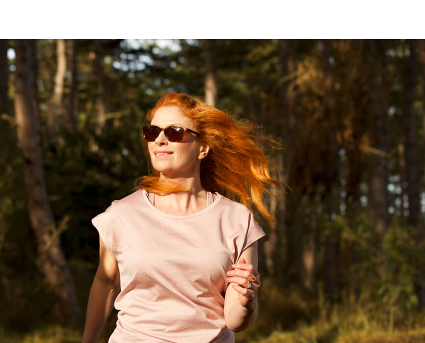 Woman with long red hair and pink top walking through woods wearing sunglasses.