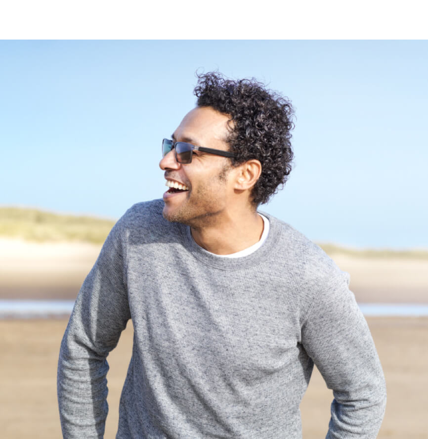 Man on beach in grey sweatshirt wearing sunglasses and looking to his right.