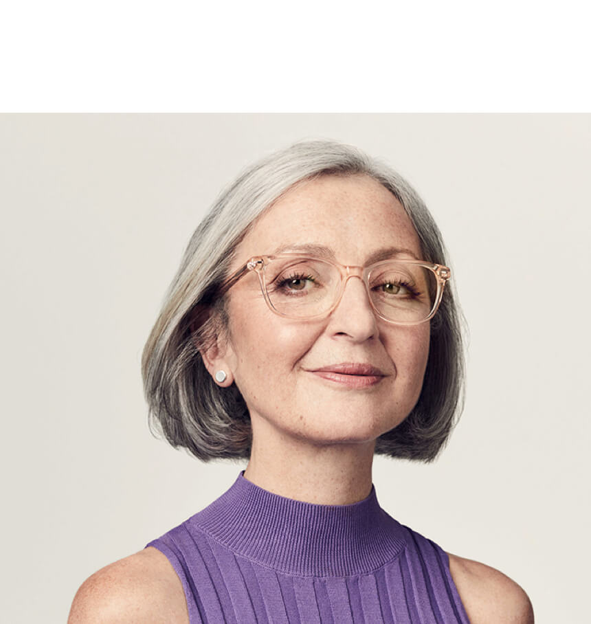 Head and shoulders of middle-aged woman with grey hair wearing a purple sleeveless top and large glasses with cleear plastic frames.