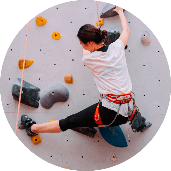 Dark haired woman in a white t-shirt and black leggings on an indoor climbing wall.
