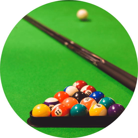 Close up of a pool cue and pool balls in a triangle on green baize.