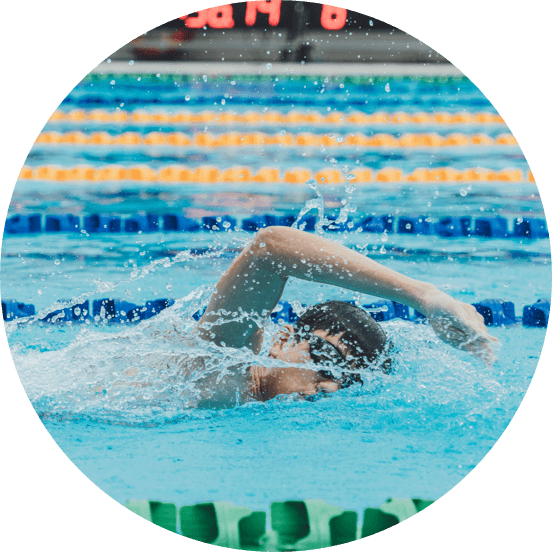 Head and arms of a man wearing goggles swimming in a competitive race.