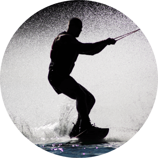 Silhouette of a man on a wakeboard being towed across water.