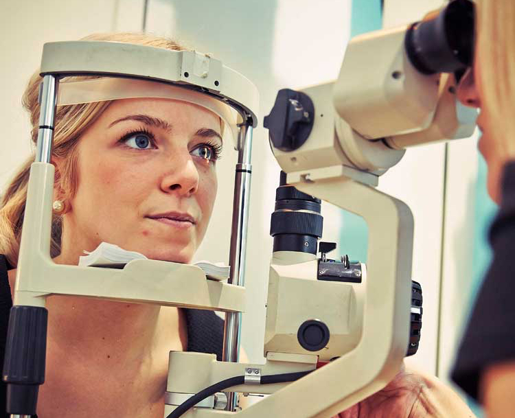 Woman with blonde hair and black top having eye test with her head placed in large piece of optical testing equipment.