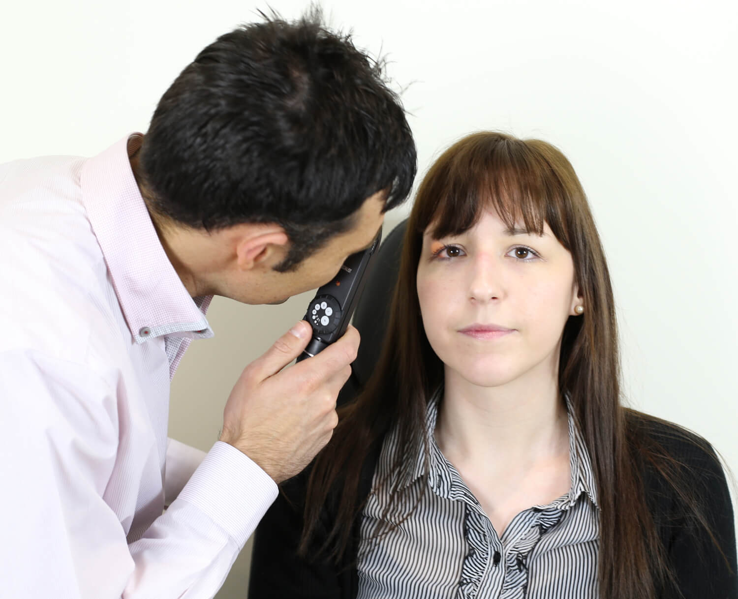 Woman with dark long hair faces forward while dark-haired optometrist looks into her eye using optical equipment during aftercare checkup.