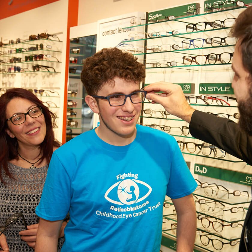 Young male in blue t-shirt standing in Vision Express store having glasses placed on his face.