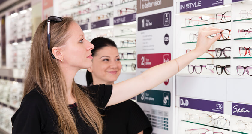 A woman with blonde hair choosing a pair of glasses with a smiling dark haired woman by her side.
