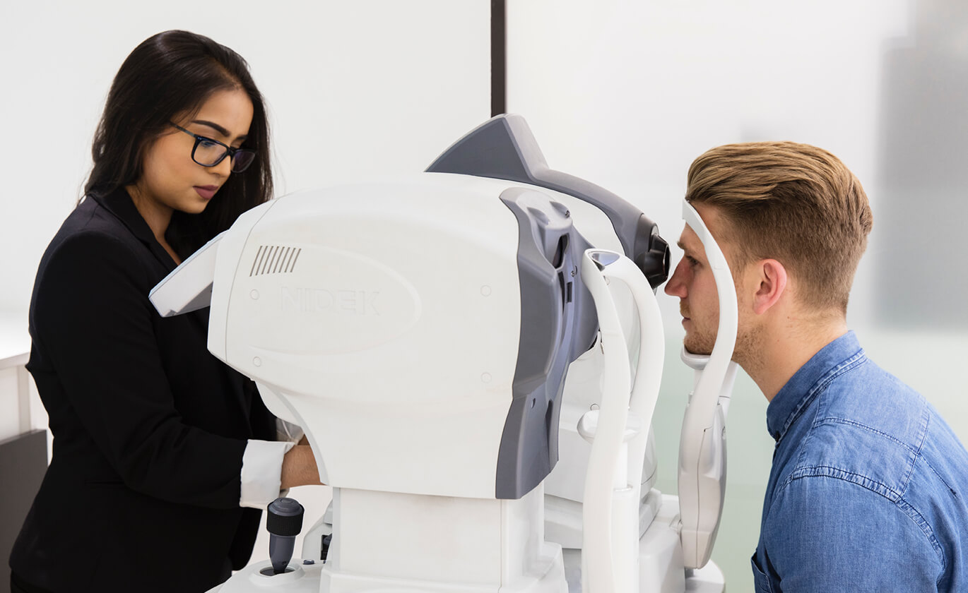 A woman with dark hair and a man with blond hair looking into eye testing equipment.