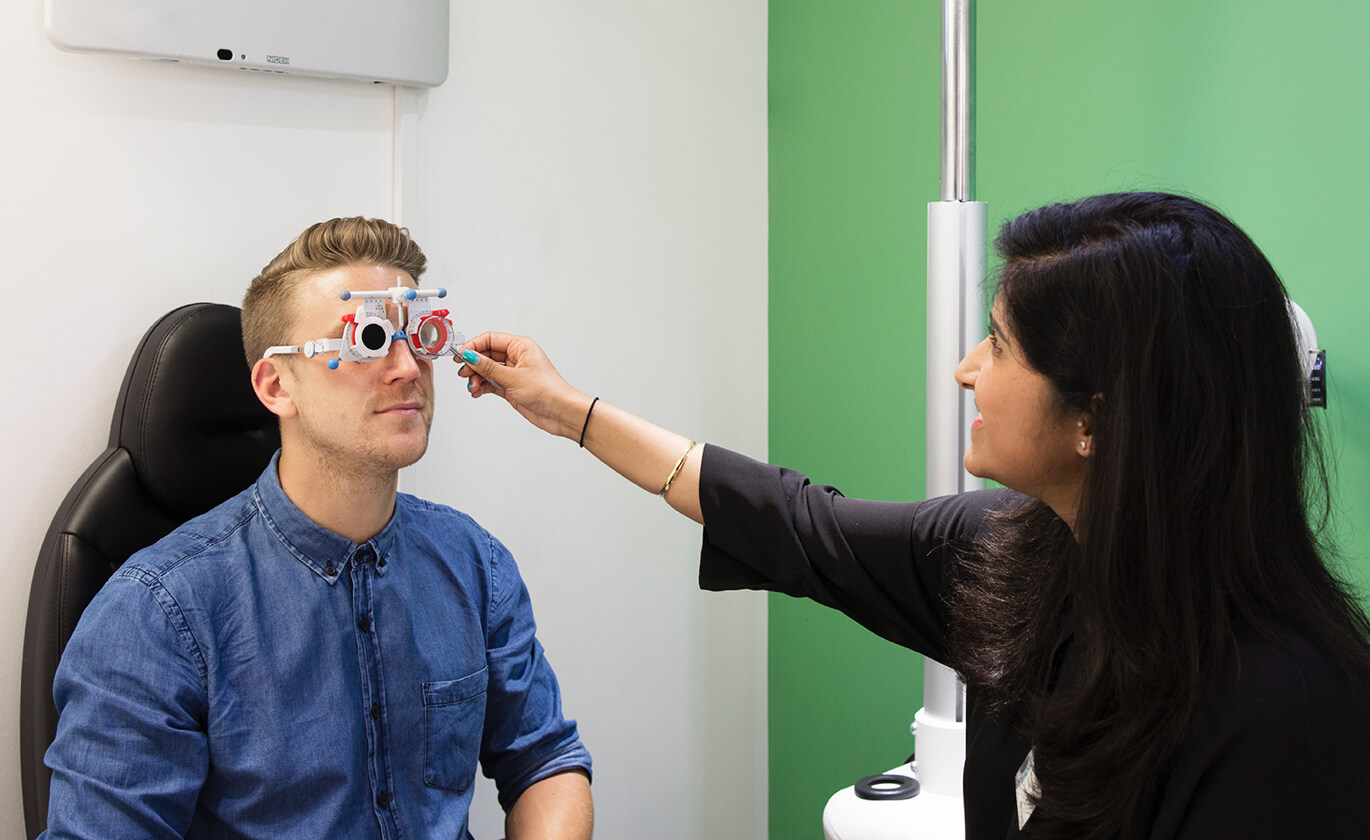A man with blond hair wearing optometrist trial frame having his eyes checked by a woman with dark hair.