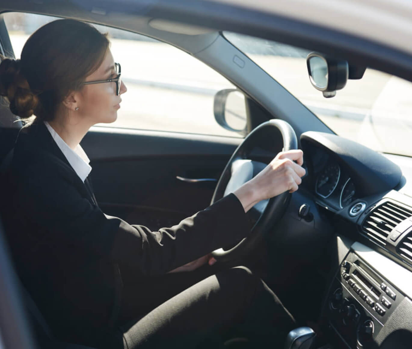 Woman with dark brown hair driving wearing black glasses.