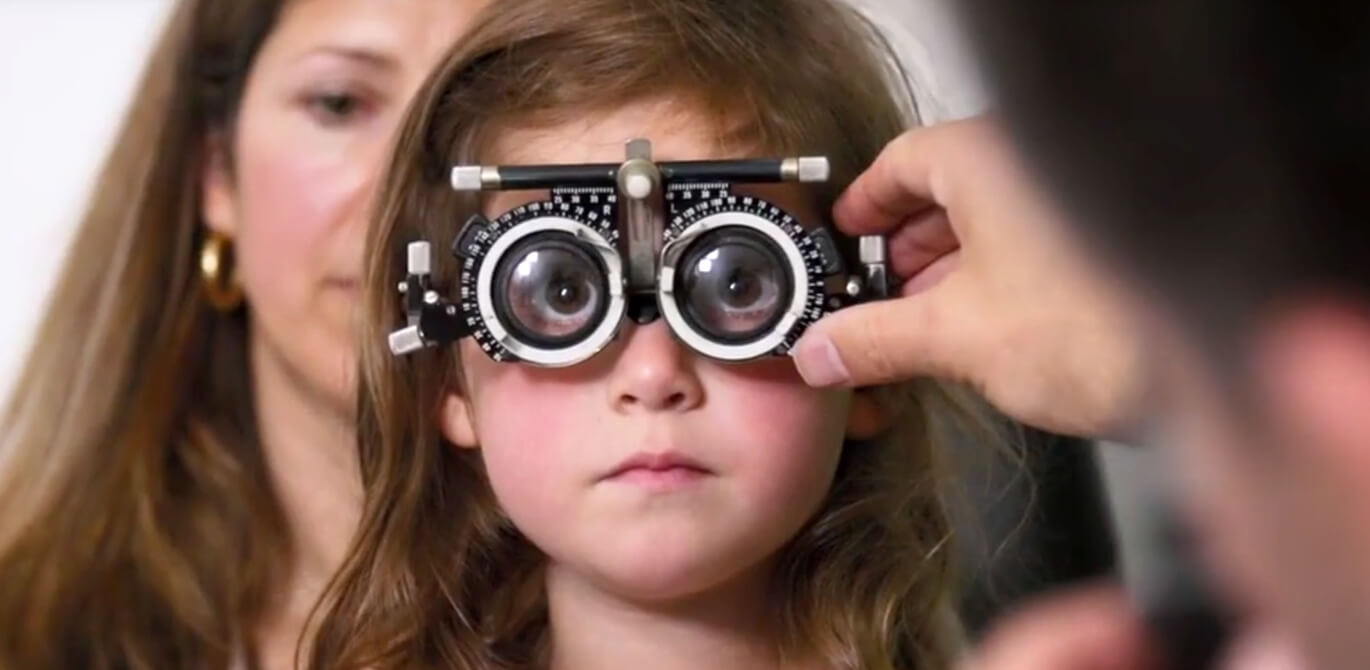 Young girl with long hair looking through testing equipment while having children's eye test.