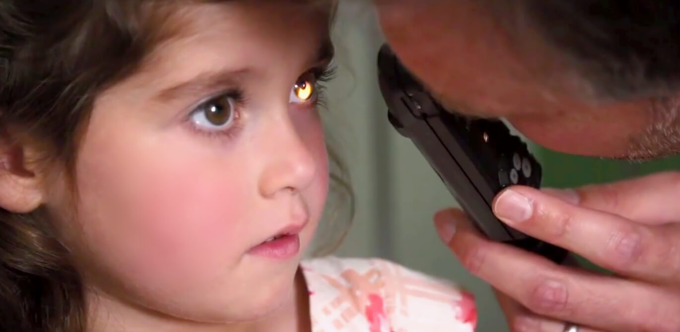 Close-up of young girl having eyes examined by male shining a light into her left eye.