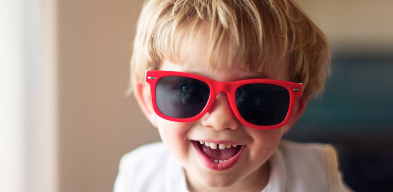 Head shot of smiling young boy with blond hair wearing a pair of red sunglasses.