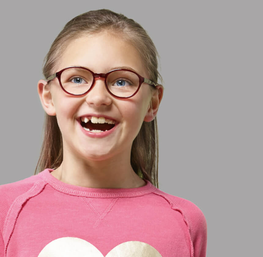 Smiling long-haired young girl with prescription glasses in red frames wearing pink sweatshirt