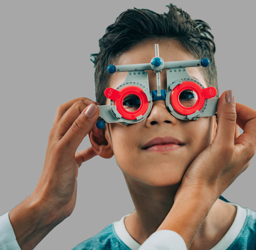 Close-up on the face of a young boy with dark hair having his eyes tested by an optician using optical equipment.