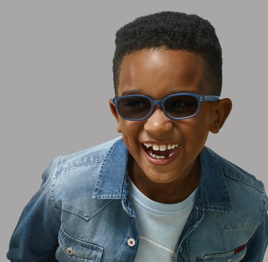 Head and shoulders of a smiling young boy with short hair wearing blue children's sunglasses, a white t-shirt and a denim jacket.