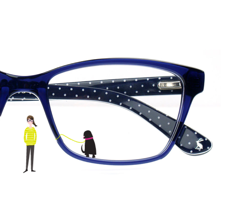 A partial view of a blue, black and polka dot pair of Joules glasses with an illustration of woman in a green top and a black dog.