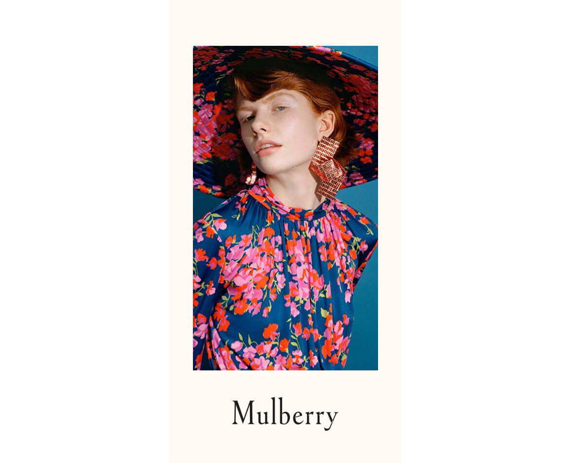 Woman with red hair wearing a pink and blue floral print Mulberry hat and matching dress.