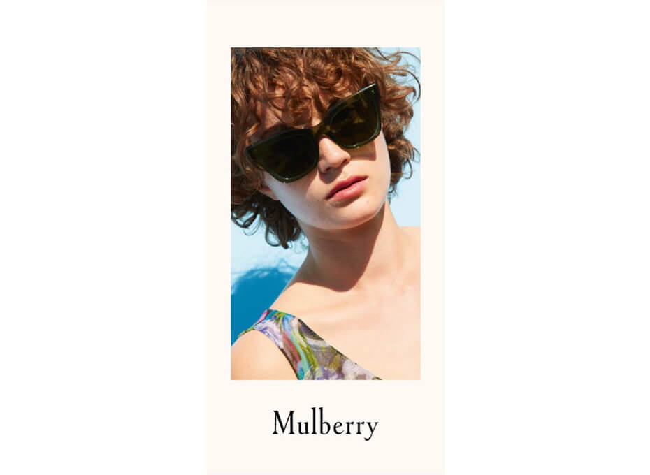 Woman with red hair against a blue background  wearing a large pair of Mulberry sunglasses.