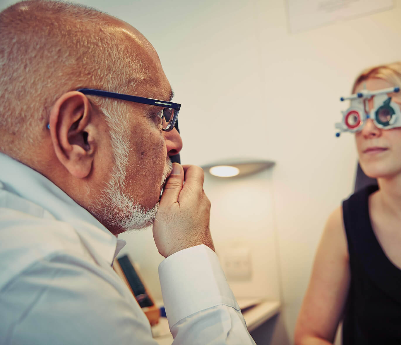 A blonde-haired woman having her eyes tested by a bespectacled and bearded optometrist.