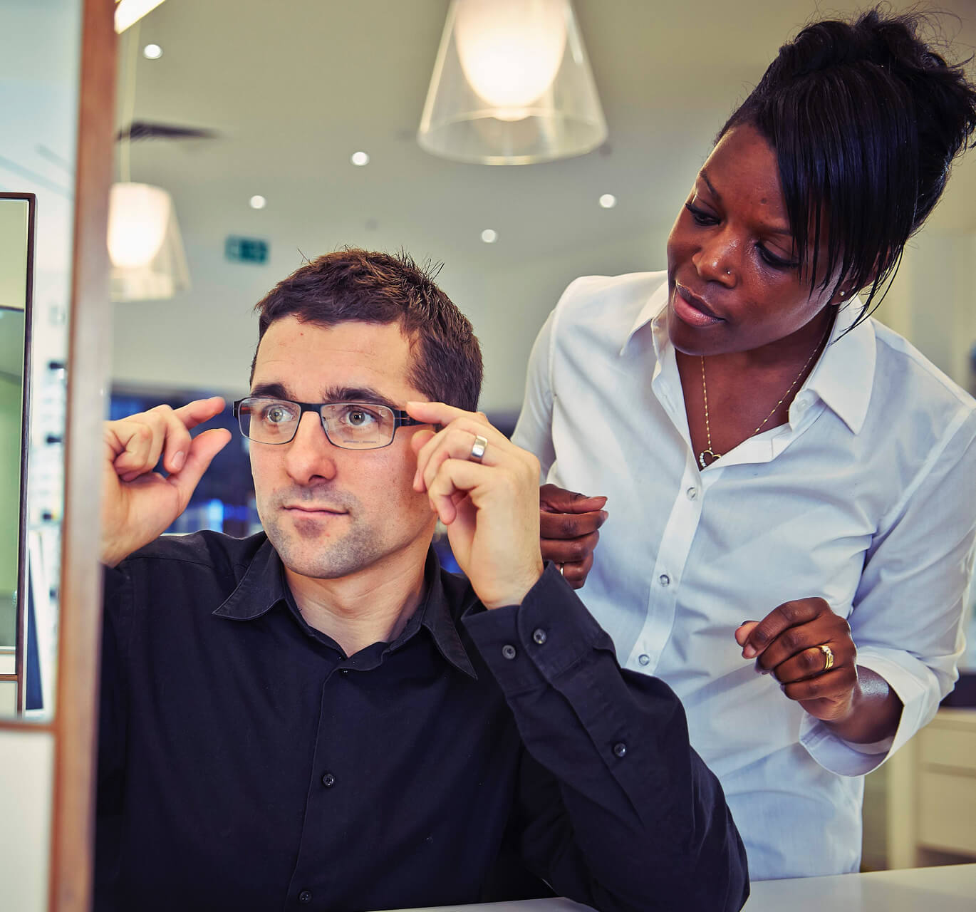 A man with dark hair and a dark blue shirt sits trying on a pair of prescription glasses while a woman in a white blouse stands behind him.
