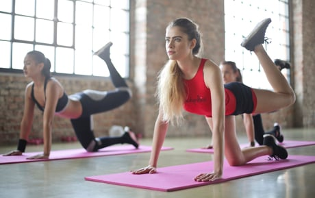 Woman in red vest with long hair taking part in yoga class.
