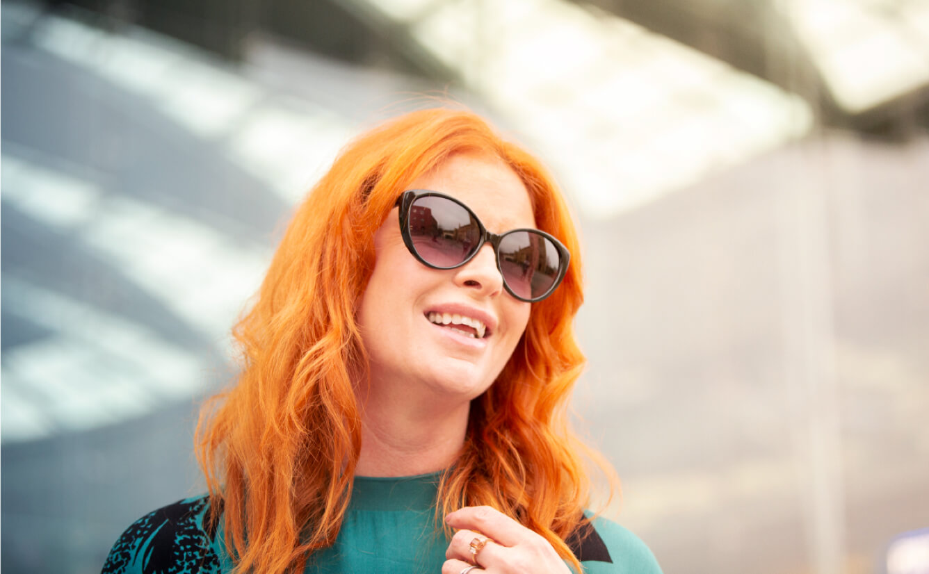 Red-headed smiling woman wearing a pair of black cats-eye sunglasses in an outdoor setting.